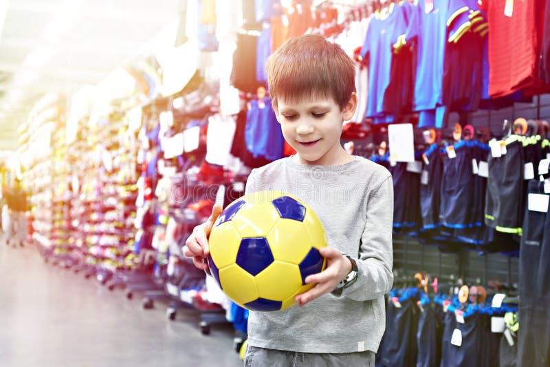 Muchacho feliz con el balón de fútbol en tienda del deporte imágenes de archivo libres de regalías