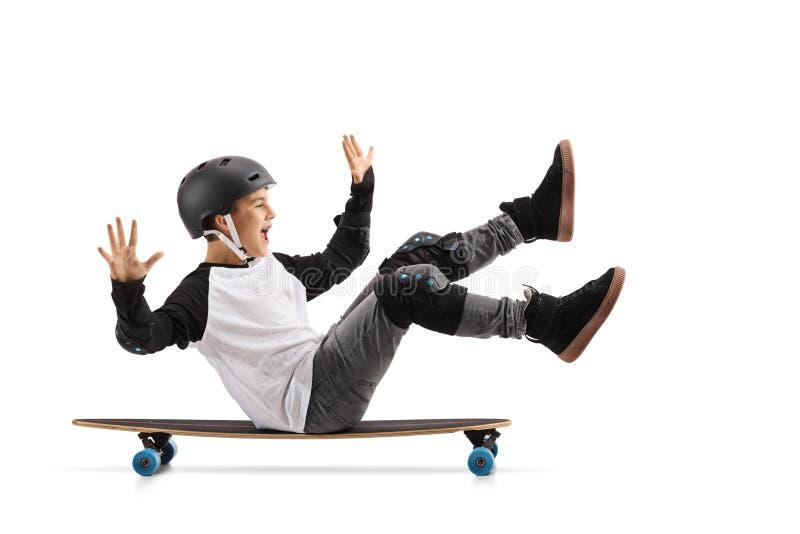 Muchacho feliz con el casco que se sienta en un longboard y montar foto de archivo libre de regalías