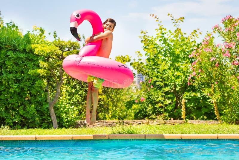 Muchacho feliz con el juguete de la nadada que salta en piscina fotografía de archivo