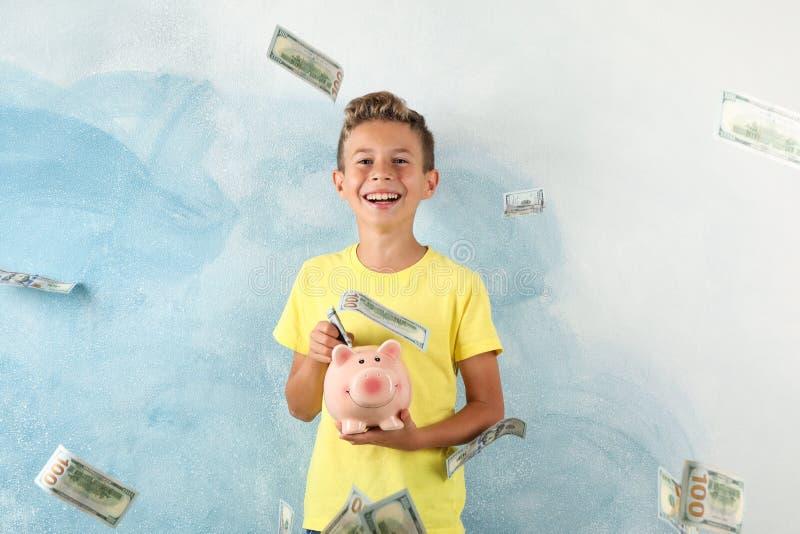 Muchacho feliz con la hucha debajo de la lluvia del dinero imagen de archivo