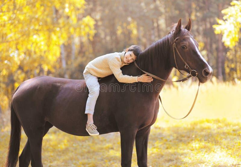Muchacho feliz del adolescente de la estación del otoño en el caballo imagen de archivo
