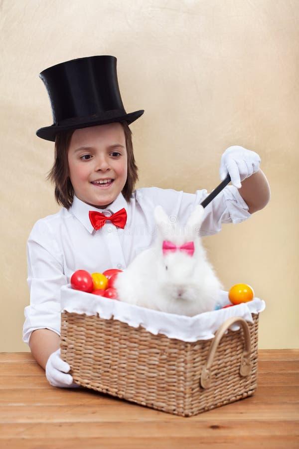 Muchacho feliz del mago que conjura un conejo de pascua y huevos coloridos foto de archivo