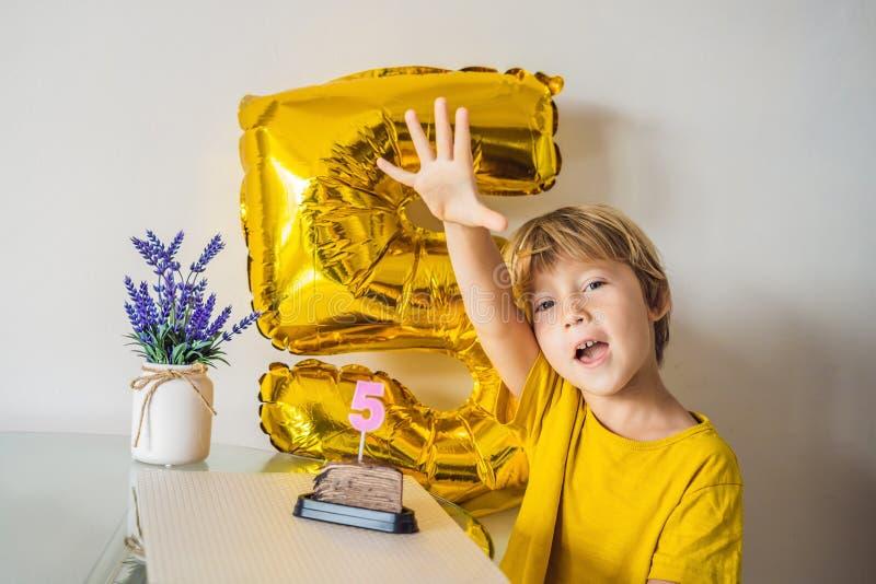 Muchacho feliz del niño que celebra su cumpleaños y que sopla velas en la torta cocida hecha en casa, interior Fiesta de cumpleañ foto de archivo