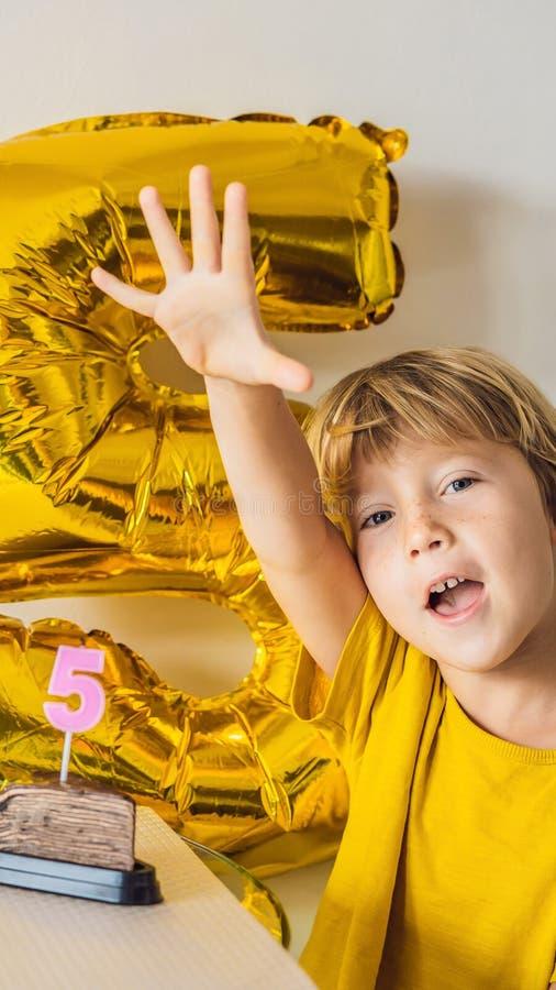 Muchacho feliz del niño que celebra su cumpleaños y que sopla velas en la torta cocida hecha en casa, interior Fiesta de cumpleañ foto de archivo libre de regalías