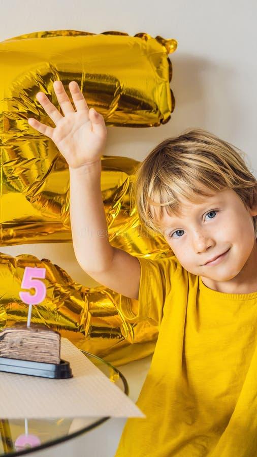 Muchacho feliz del niño que celebra su cumpleaños y que sopla velas en la torta cocida hecha en casa, interior Fiesta de cumpleañ imagen de archivo