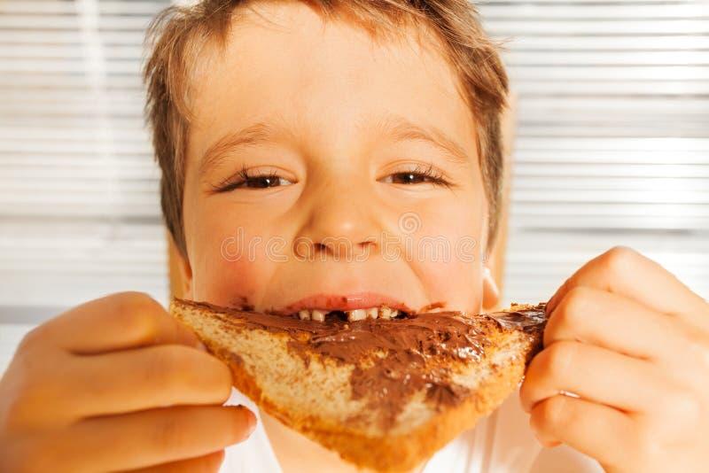 Muchacho feliz del niño que come la tostada con la extensión del chocolate fotos de archivo