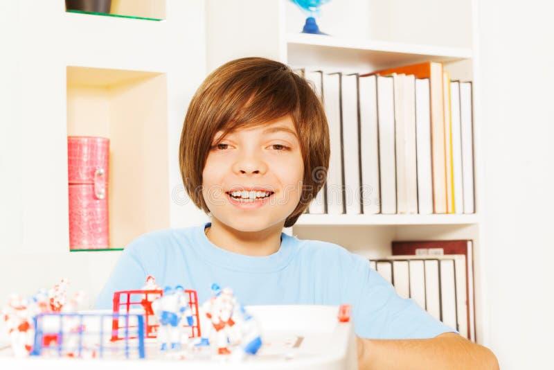 Muchacho feliz del niño que juega al juego de mesa de la tabla del hockey sobre hielo foto de archivo