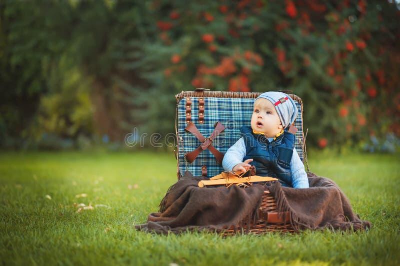 Muchacho feliz del niño que juega con el juguete del aeroplano mientras que se sienta en maleta en césped verde del otoño Niños q fotos de archivo