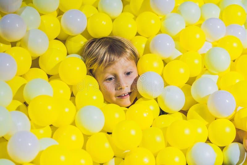 Muchacho feliz del niño que juega en el playgroun plástico colorido de las bolas imagen de archivo