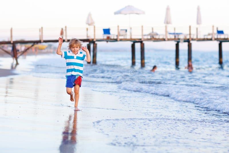 Muchacho feliz del niño que se divierte con el funcionamiento a través del agua en Oc fotos de archivo