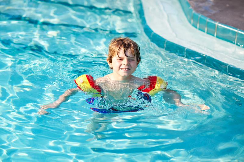 Muchacho feliz del niño que se divierte en una piscina Niño preescolar feliz activo que aprende nadar con los floaties seguros fotografía de archivo