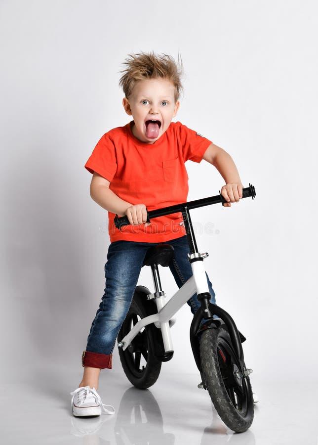 Muchacho feliz del niño sentar y montar su bicicleta con el motorista gritador de grito que celebra su triunfo en raza fotografía de archivo