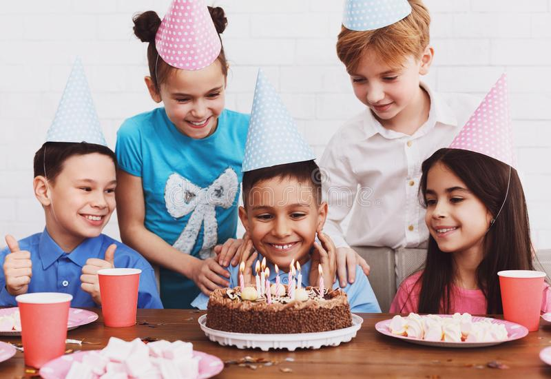 Muchacho feliz en sombrero del partido con la torta de cumpleaños foto de archivo libre de regalías