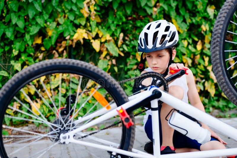 Muchacho feliz en un casco de la bicicleta que repara su bici imágenes de archivo libres de regalías