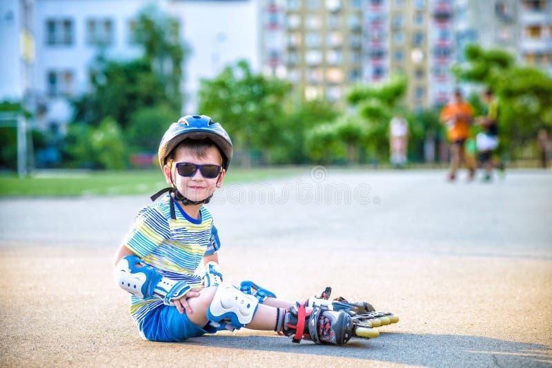 Muchacho feliz en un casco protector y cojines protectores para el patinaje sobre ruedas Espacio para el texto foto de archivo