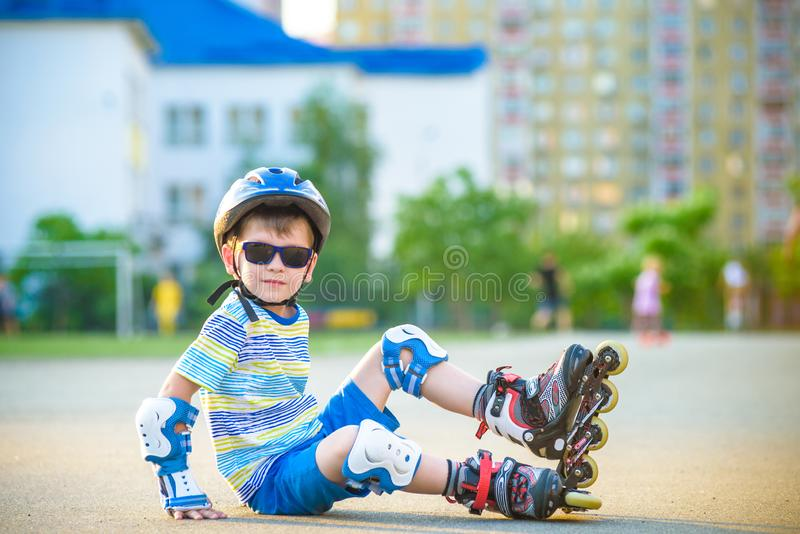 Muchacho feliz en un casco protector y cojines protectores para el patinaje sobre ruedas Espacio para el texto imágenes de archivo libres de regalías