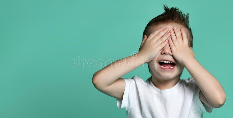 Muchacho feliz joven con el pelo marrón que grita y que cubre ojos con las manos imágenes de archivo libres de regalías
