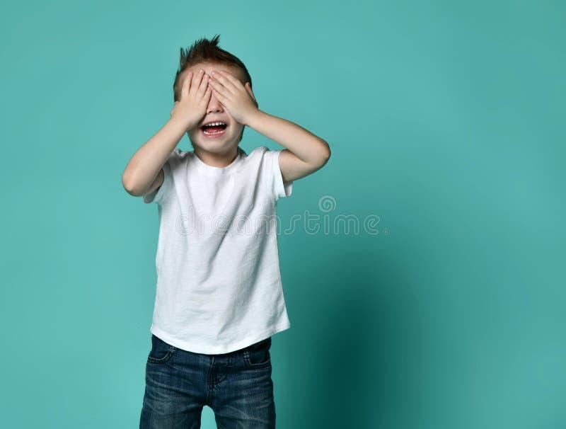 Muchacho feliz joven con el pelo marrón que grita y que cubre ojos con las manos imagen de archivo