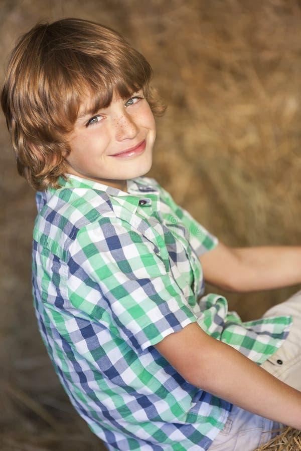 Muchacho feliz joven que sonríe en Hay Bales imagen de archivo libre de regalías