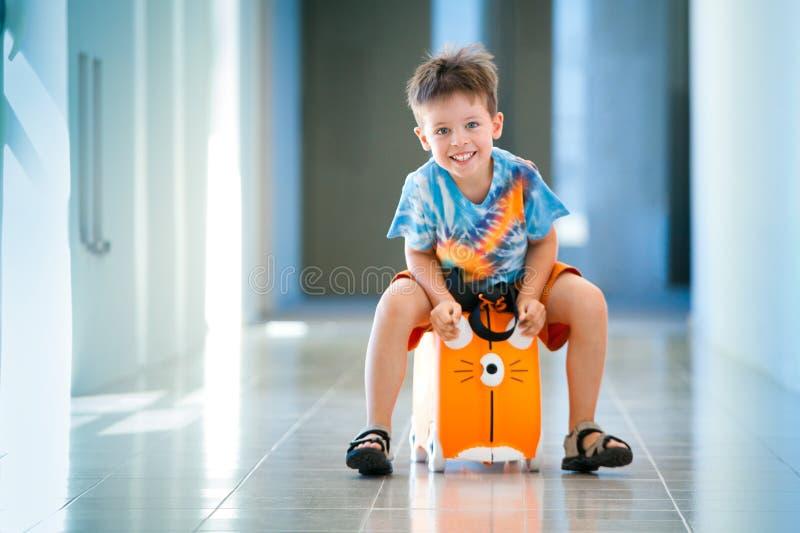 Muchacho feliz lindo con una maleta en el aeropuerto imagen de archivo libre de regalías