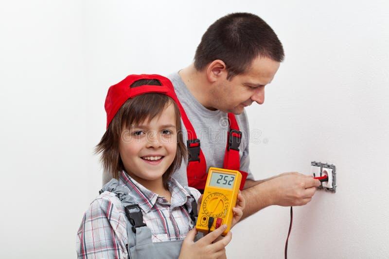 Muchacho feliz que ayuda a su padre que monta los accesorios eléctricos de la pared foto de archivo libre de regalías