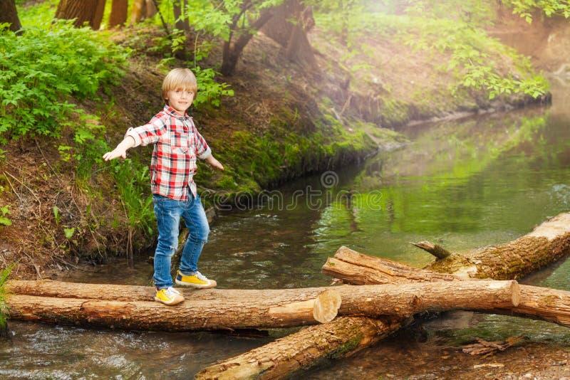 Muchacho feliz que cruza un río en el bosque foto de archivo libre de regalías