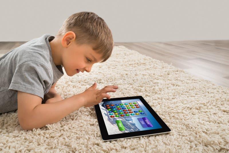 Muchacho feliz que juega al juego en la tableta de Digitaces fotografía de archivo