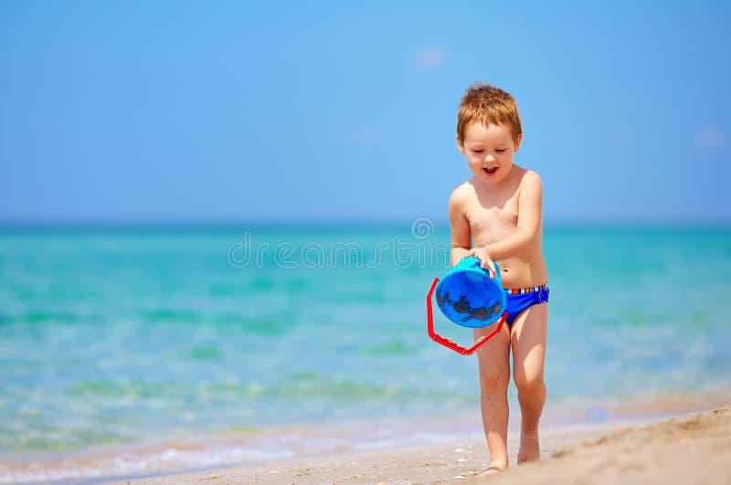 Muchacho feliz que juega con los juguetes en la playa imagen de archivo