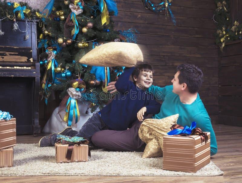 Muchacho feliz que juega con su padre en la Navidad fotos de archivo