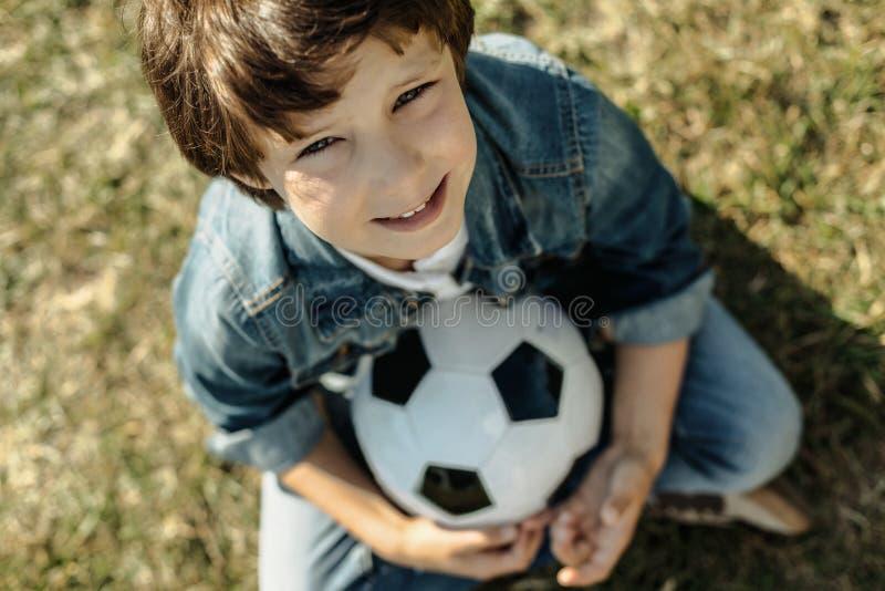 Muchacho feliz que se sienta con su bola fotos de archivo libres de regalías