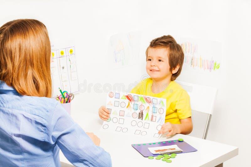 Muchacho feliz que sostiene el dibujo con formas coloreadas foto de archivo