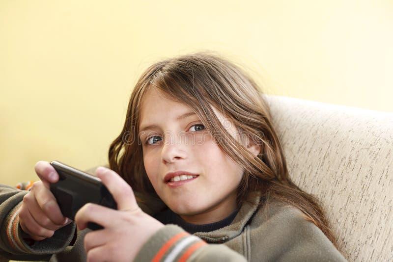 Muchacho feliz que usa un teléfono elegante foto de archivo libre de regalías