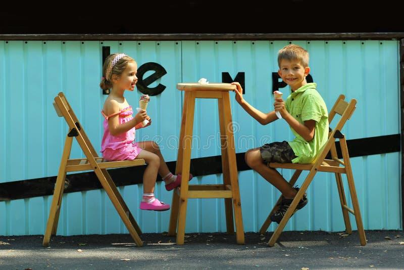 Muchacho feliz y muchacha, hermano y hermana, comiendo el helado en el café al aire libre de la ciudad de la acera del aire abier imagen de archivo