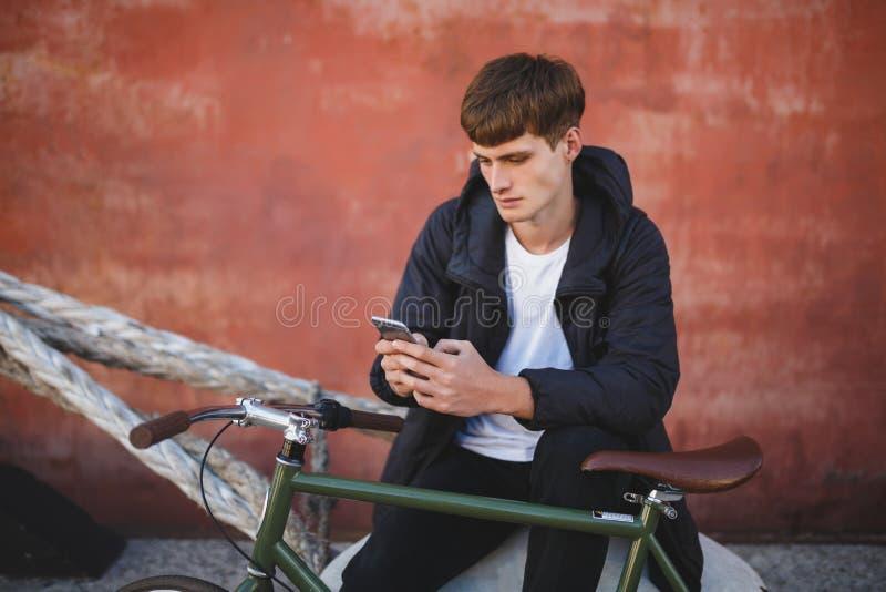Muchacho fresco con la sentada marrón y usar del pelo su teléfono móvil Hombre joven en abajo la chaqueta y la camiseta blanca qu fotografía de archivo