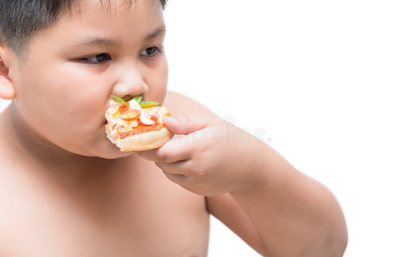 Muchacho gordo obeso que come la pizza de los mariscos imagen de archivo libre de regalías