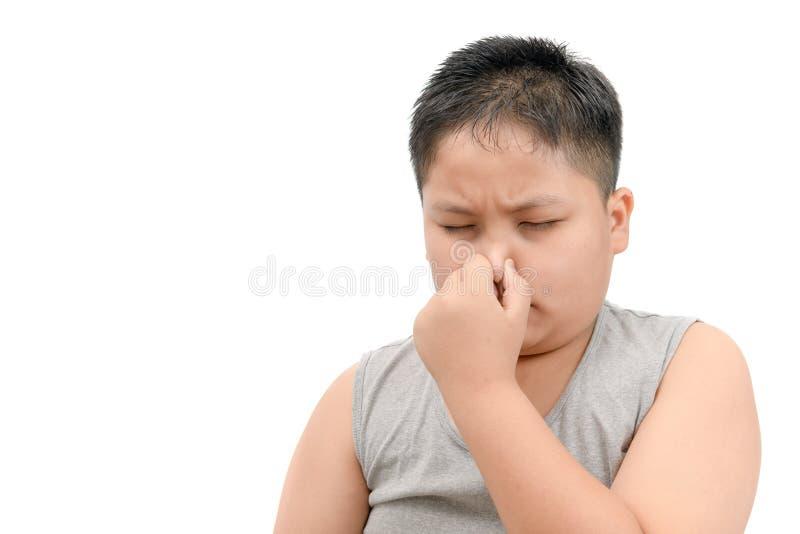 Muchacho gordo que cubre su nariz debido a un mún olor asqueroso imágenes de archivo libres de regalías