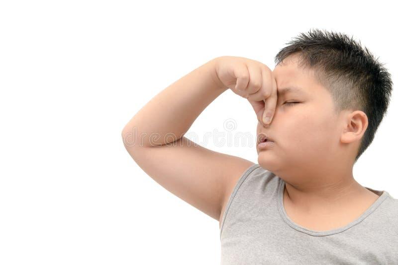 Muchacho gordo que cubre su nariz debido a un mún olor asqueroso fotos de archivo