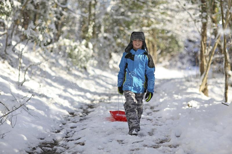 Muchacho hacia fuera sledding en la nieve foto de archivo libre de regalías