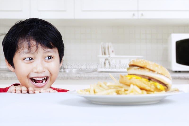 Muchacho hambriento que mira la hamburguesa de la carne de vaca imagen de archivo libre de regalías