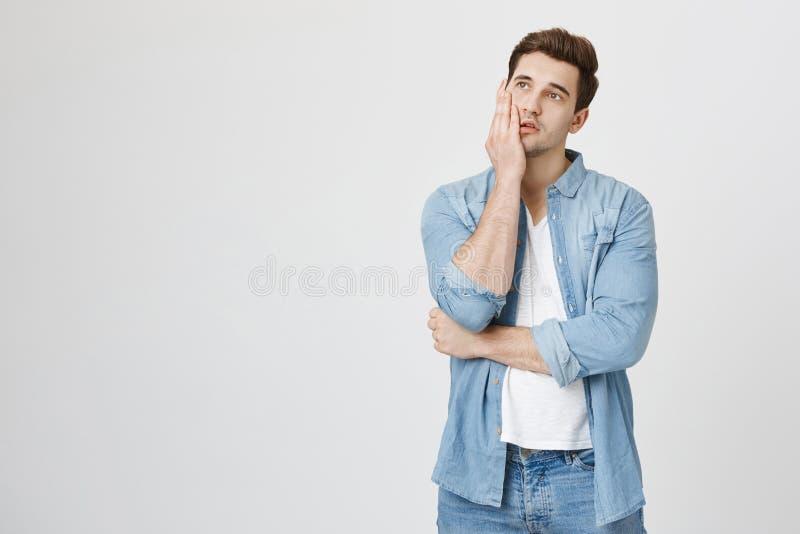 Muchacho hermoso cansado y enfadado que sostiene la palma en mejilla y que mira para arriba, expresando el aburrimiento mientras  imagen de archivo libre de regalías