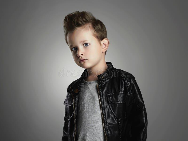 muchacho hermoso con el peinado de moda nio de moda en la capa de cuero foto