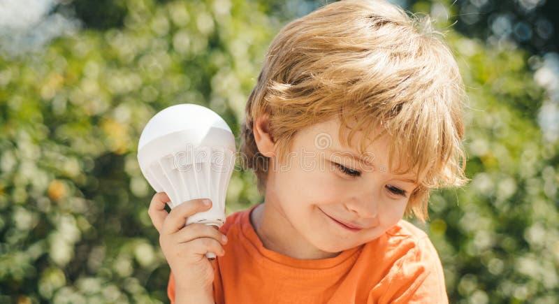 Muchacho hermoso con una bombilla Un explorador elaborado Las lecciones de la física Poco muchacho elegante del científico A ense fotografía de archivo