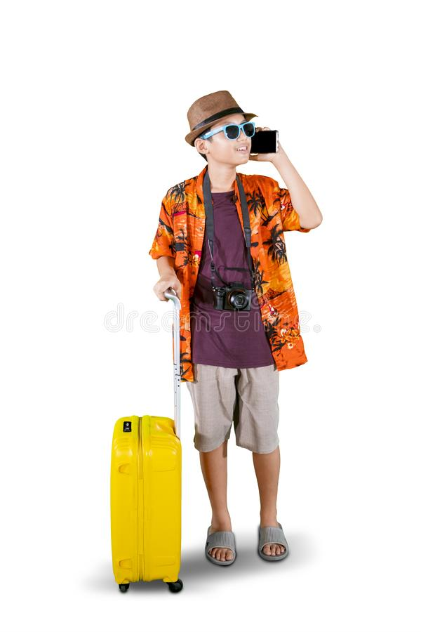 Muchacho hermoso del preadolescente con el teléfono y el equipaje fotos de archivo libres de regalías