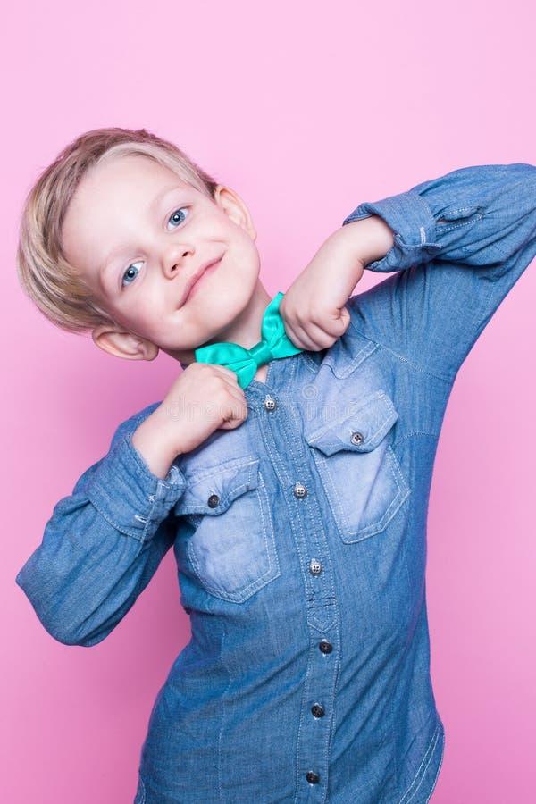 Muchacho hermoso joven con el lazo azul de la camisa y de mariposa Retrato del estudio sobre fondo rosado imagenes de archivo