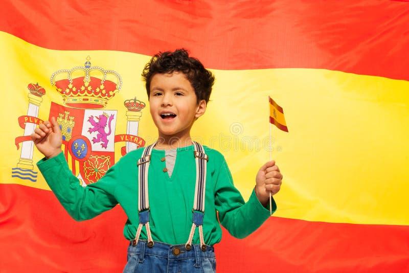 Muchacho hispánico feliz con la bandera española en su mano fotos de archivo libres de regalías