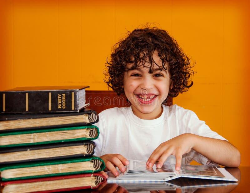 Muchacho hispánico feliz que mira las fotos de familia viejas fotos de archivo libres de regalías