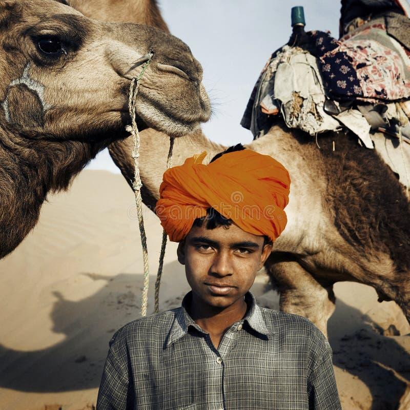 Muchacho indio joven con concepto del desierto de los camellos fotografía de archivo