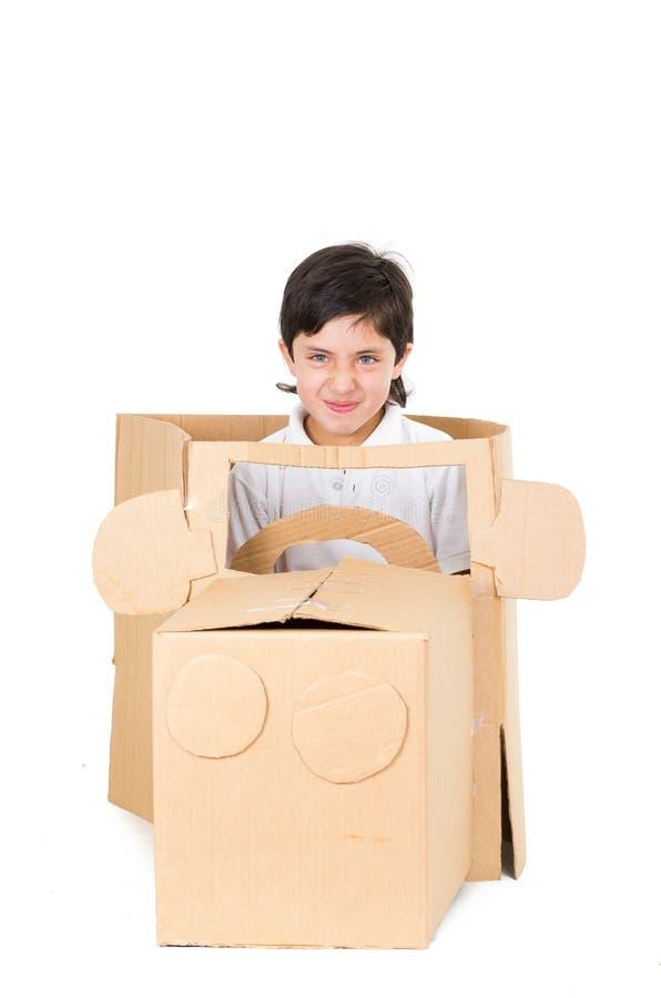 Muchacho joven adorable que se sienta en un coche de la cartulina imagen de archivo