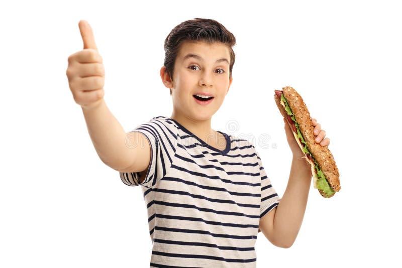 Muchacho joven alegre que sostiene un bocadillo y que da un pulgar para arriba imágenes de archivo libres de regalías