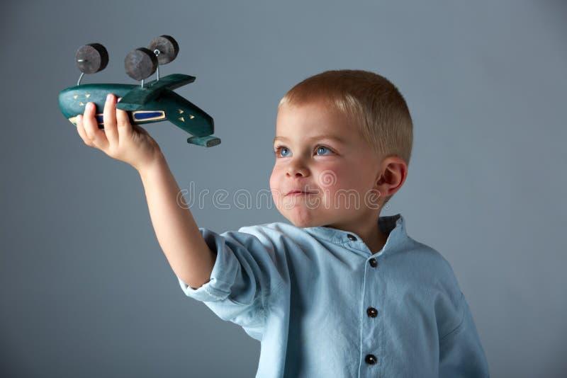 Muchacho joven con el aeroplano de madera imagen de archivo libre de regalías